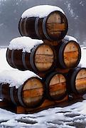 A pile of Oak wood wine barrels in the snow
