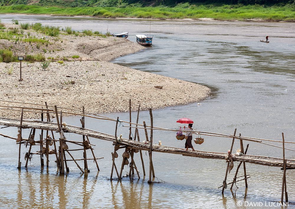 A woman crossing a wooden bridge over Nam Khan River in the midday heat. At the same time a fisherboat is cruising at the confluence of Nam Khan River and the Mekong River.