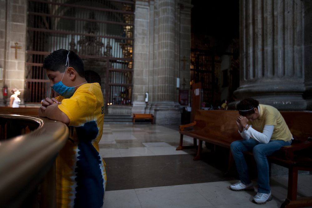 24 April 2009, Mexico City, Mexico--- A  boy wearing a surgical mask prays at the    Metropolitan Cathedral  in the center of Mexico City. The Government has recommended that people wear the masks to protect themselves from a deadly strain of Swine Flu that has alread killed 60 people and made 1008 sick. The Swine Flu which has also been found elsewhere in Mexico and the USA is extremely worrying to the WHO, and CDC who belive that it could cause a Flu Pandemic. The disease tends to kill young healthy people, which is common with a Pandemic Flu.  The  --- Image by © Trevor Snapp
