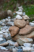 Stone markers left by hikers on the bank of the stream in Stubai, Tyrol, Austria