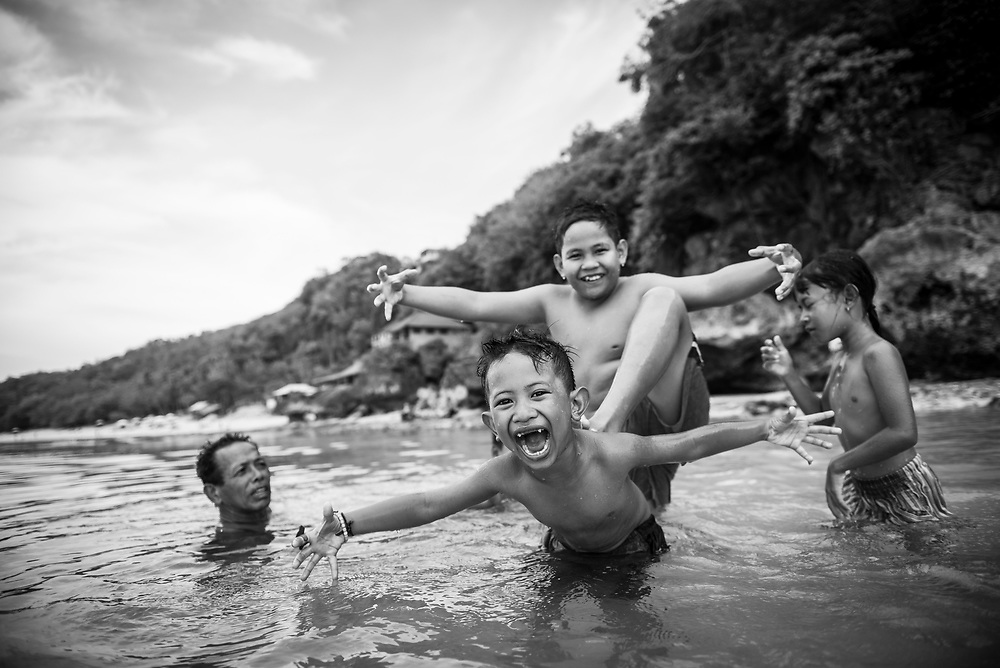Bali, Indonesia - February 26, 2017: Indonesian kids, swimming with an adult at Thomas Beach on the island of Bali, play with one another and react to a passing photographer's camera.
