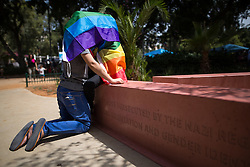 "© Licensed to London News Pictures . 03/06/2016 . Tel Aviv , Israel . Two women shelter beneath a rainbow flag at a memorial for LGBT people who were persecuted by the Nazis , at Meir Park at the start of the parade . Over 100,000 people attend the gay pride parade in Tel Aviv , reported to be the largest such event in the Middle East and Asia . The Israeli government has been accused of using the event as "" pinkwashing "" , marketing the event in order to deflect accusations of poor human rights behaviour . Photo credit: Joel Goodman/LNP"