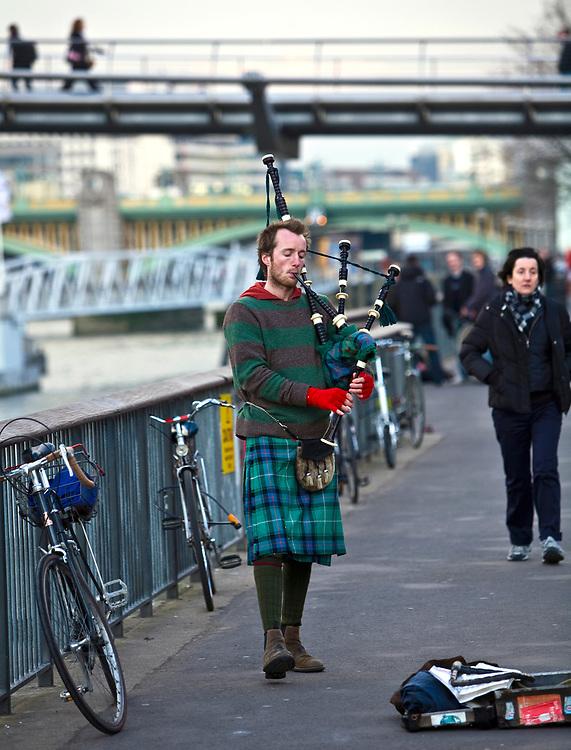 Londyn, 2009-03-05. Uliczny muzyk na bulwarach Tamizy