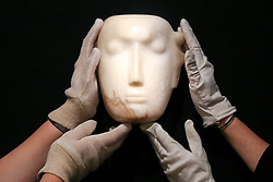 """© Licensed to London News Pictures. 12/11/2018. London, UK. Staff members holds """"The Man Behind the Mask"""", a Henry Moore'smasterpiece (British, 1898-1986). (Estimate: £1,000,000-1,500,000). The work is one of 12 known, small carvings by Moore titled Mask, and, uniquely, is the only one carved from alabaster.<br /> Bonhams Modern British and Irish Art photocall. Auction to be held on 14 November 2018. Photo credit: Dinendra Haria/LNP"""