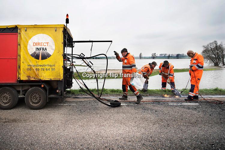Nederland, Overbetuwe, 6-3-2020  Op de dijk is een wegenbouwbedrijf, bezig met het asfalteren van de rand van het wegdek en het dichten van scheuren in het wegdek die ontstaan zijn door de droogte. Door de scheuren kan er onnodig veel water in het dijlichaam zakken waardoor dit verzwakt . De randen zijn vervelend voor fietsers die na uitwijken in de berm belanden en dan kunnen vallen vanwege de afgesleten rand. Foto: Flip Franssen