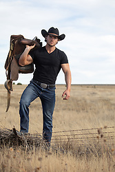 cowboy with a saddle on a rural ranch