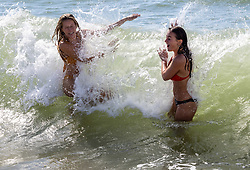 Licensed to London News Pictures. 23/09/2021. Brighton, UK. Swimmers Millie Podmore 22 and Rose McKinnel 21 enjoy a splash in the sea at Brighton, Sussex as weather forecasters predict warm autumnal weather to continue for the weekend with highs of 24c. Photo credit: Alex Lentati/LNP