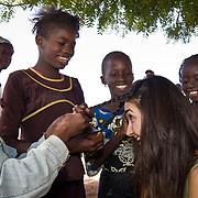 Girls from Koumbadiouma delight in braiding Peace Corps volunteer Rachael's hair during the Sunday market. Kolda, Senegal.