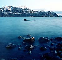 Utsikt mot Godøya og et snøkledt Godøyfjell sett fra Kvalneset på Giske i Giske kommune. Til høyre i bildet ser man Alnes.<br /> <br /> View towards Godøy mountain and Alnes seen from Kvalneset at Giske in Norway.<br /> Foto: Svein Ove Ekornesvåg