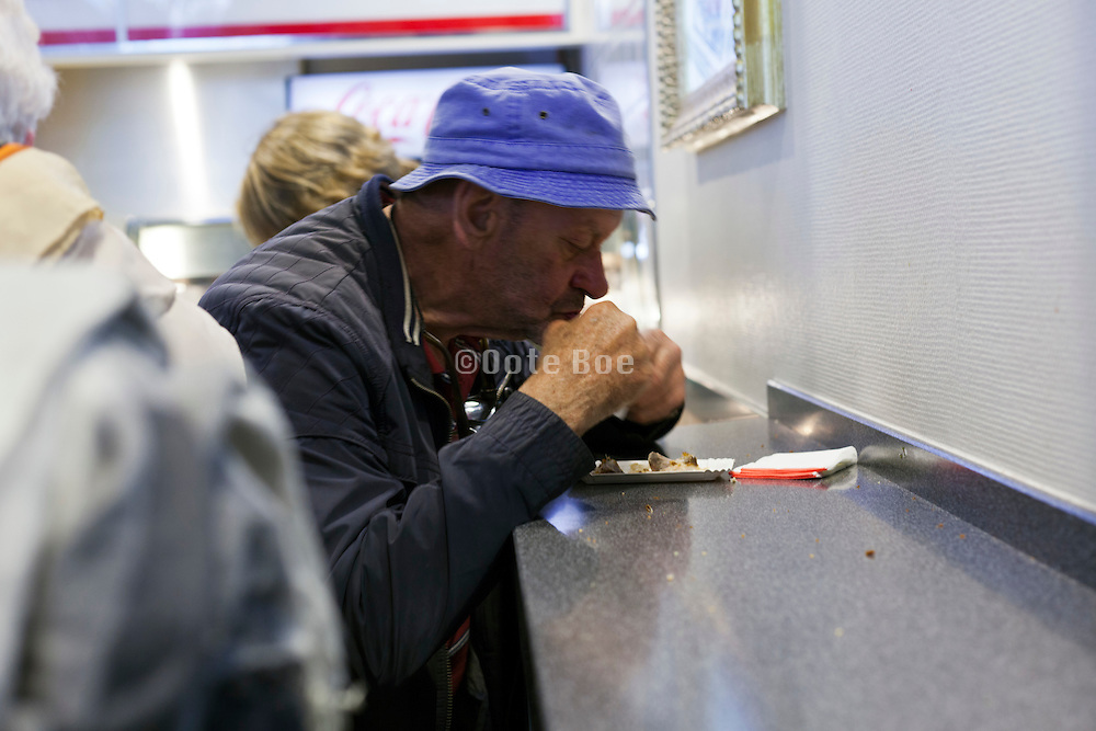 man eating fast food in snack bar