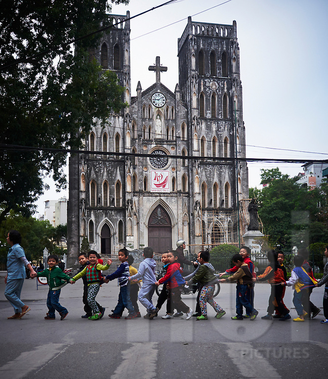 A group of pupils cross the street in front of St Joseph Cathedral, Hanoi, Vietnam, Southeast Asia