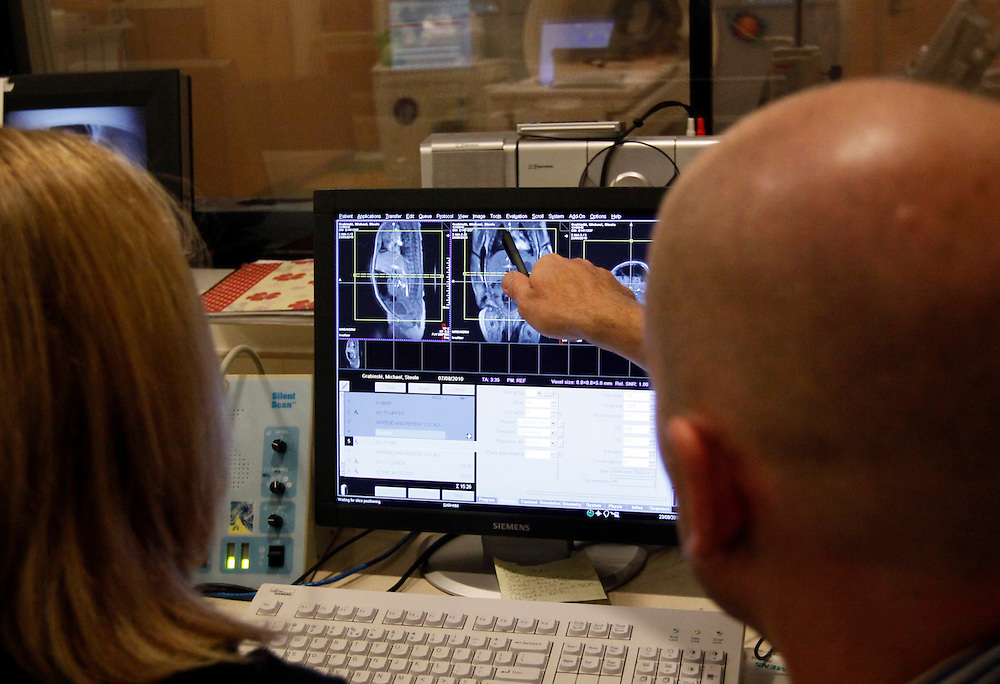 Dr. David Brumbaugh (R) and Claire Skold, MRI Technologist looks at live MRI images of Michael Grabinski, (background) two weeks old at The Children's Hospital in Aurora, Colorado August 23, 2010 during a research study on obesity in infants. The overall theme of the study is to understand the continuum of growth that starts really at conception, and to understand if the earliest phases of growth impacts later risk for obesity.   REUTERS/Rick Wilking (UNITED STATES)