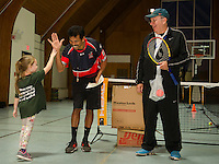 Evie gets a high five from Coach Kamal Gosine with Coach Bob Rondstat during their tennis club graduation at the Laconia Boys and Girls Club. (Karen Bobotas/for the Laconia Daily Sun)