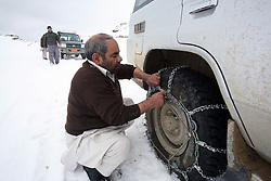 NCA drivers and vehicles on the road from Bamyan to Sharestan stop to put on snow chains as they travel to project sites, Afghanistan