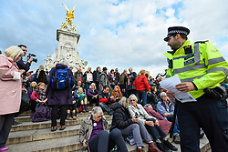 © Licensed to London News Pictures. 15/10/2019. LONDON, UK. A police officer reads out a Section 14 notice to climate activists from Extinction Rebellion stage a Grandparents protest on Queen Victoria Memorial outside Buckingham Palace.  Activists are calling on the government to take immediate action against the negative effects of climate change.  Photo credit: Stephen Chung/LNP