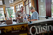 Roger Lefebvre, left, provides Roberta Omera of Thatcher, AZ with local real estate brochures at the Coeur d'Alene Visitor Center on Thursday.