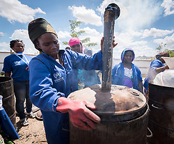 30 May 2019, Mokolo, Cameroon: Aisha Bukar closes the metal container in which biomass is burnt, in preparation to become charcoal. At the Minawao camp for Nigerian refugees, degradable and non-degradable waste are separated, so that biomass can be burnt in metal containers, processed and finally transformed into charcoal briquettes as a source of recycled energy to be used as firewood for cooking. With the support of an environment monitor  from the Lutheran World Federation World Service programme, the full process from waste to charcoal is managed and run by the refugees themselves. The Minawao camp for Nigerian refugees, located in the Far North region of Cameroon, hosts some 58,000 refugees from North East Nigeria. The refugees are supported by the Lutheran World Federation, together with a range of partners.
