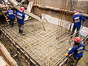 "23 AUGUST 2013 - BANGKOK, THAILAND:    Workers pour concrete on a construction site in Bangkok. Thailand entered a ""technical"" recession this month after the economy shrank by 0.3% in the second quarter of the year. The 0.3% contraction in gross domestic product between April and June followed a previous fall of 1.7% during the first quarter of 2013. The contraction is being blamed on a drop in demand for exports, a drop in domestic demand and a loss of consumer confidence. At the same time, the value of the Thai Baht against the US Dollar has dropped significantly, from a high of about 28Baht to $1 in April to 32THB to 1USD in August.    PHOTO BY JACK KURTZ"