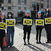 Chinese students wearing face coverings holding a 2 m distance sign to alert to the rise of #covid19 infection in the UK.