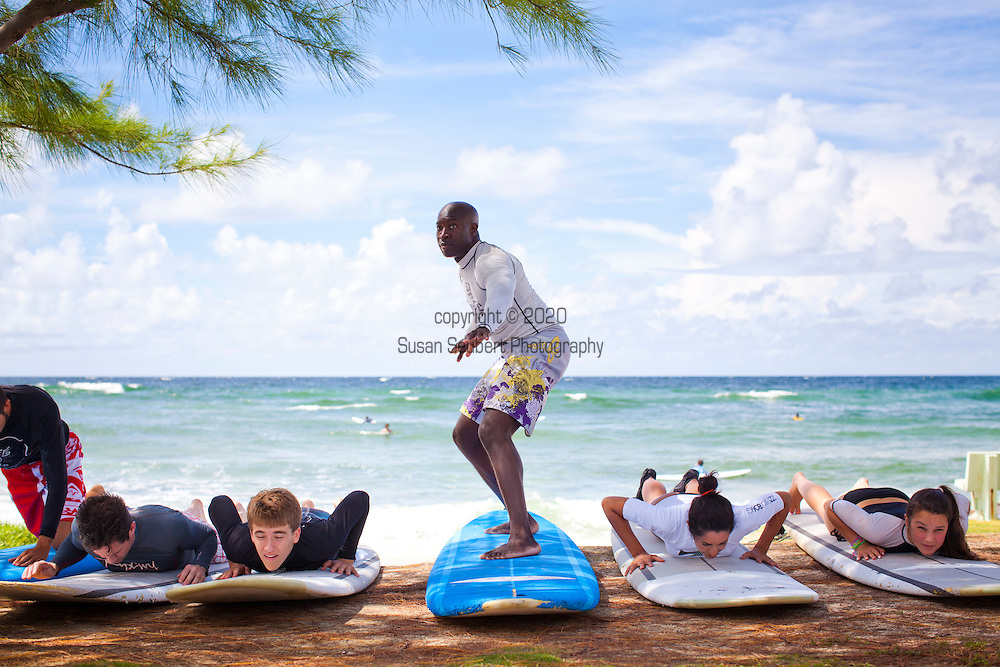 Zed's surf school at Surfer's Point on the South Coast of Barbados.  A group of people taking the land part of the learning to surf class