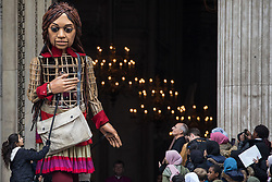 London, UK. 23rd October, 2021. Little Amal, a giant puppet of a Syrian refugee girl fleeing conflict, leaves St Paul's Cathedral after being welcomed by a crowd including many children. The 3.5-metre puppet, which is nearing the end of an 8,000km journey from the Turkish-Syrian border to Manchester in support of refugees, climbed the steps of St Paul's Cathedral to present a wood carving of a ship at sea from St Paul's birthplace at Tarsus in Turkey to the dean.