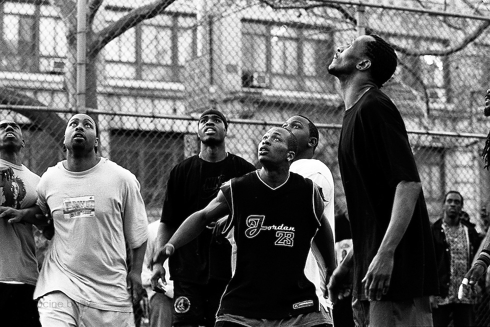 """April 6th 2005. New York, New York. United States..Located in the heart of Greenwich Village, the West 4th Street basketball Court, known as """"The Cage"""", offers no seating but attracts the best players and a lot of spectators as soon as spring is around the corner..Half the size of a regular basketball court, it creates a fast, high level of play. The more people watch, the more intense the games get. « The Cage » is a free show. Amazing actions, insults and fights sometimes, create tensions among and inside the teams. The strongest impose their rules. Charisma is present..""""The Cage"""" is a microcosm. It's a meeting point for the African American street culture of New York. Often originally from Jamaica or other islands of the Caribbean, they hang out, talk, joke, laugh, comment the game, smoke… Whether they play or not, they're here, inside """"The Cage"""". Everybody knows everybody, they all greet each other, they shake hands and hug: """"Yo, whasup man?"""""""