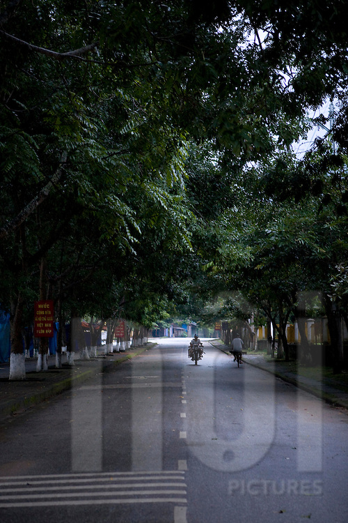 Perspective of a calm tree lined street. A motorbike and a bicycle ride the way. Yen Bai province, Vietnam, Asia.