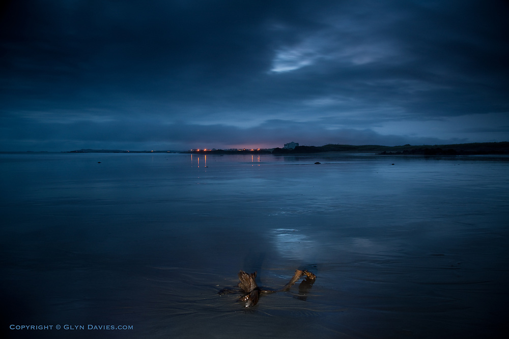 The orange glow of the street lights in Rhosneigr light up low cloud in this blue landscape. Bright patches in the rain clouds are reflected in the wet sands of Broad Beach in the foreground.