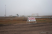 Gun shop sign in Burlington, near to Minot, North Dakota, United States. Many types of weapons are for sale here from basic shotguns and handguns to military type semi-automatics such as the M16. Guns and ammunition from this store are used by hunters and for protection.