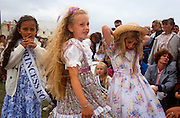 Carnival princesses with local crowds at the contest for Torbay's Carnival Princess and Queen during the seaside town's fair in Devon, England. Three young girls dressed in floral dresses await decisions near their eager families. Some wear a special sash with 'Princess for a day' across.