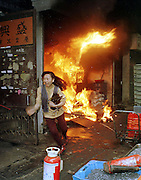 A woman escapes from a fire in a factory in Hunghom. Hong Kong (??/93) photo by Ringo Chiu.