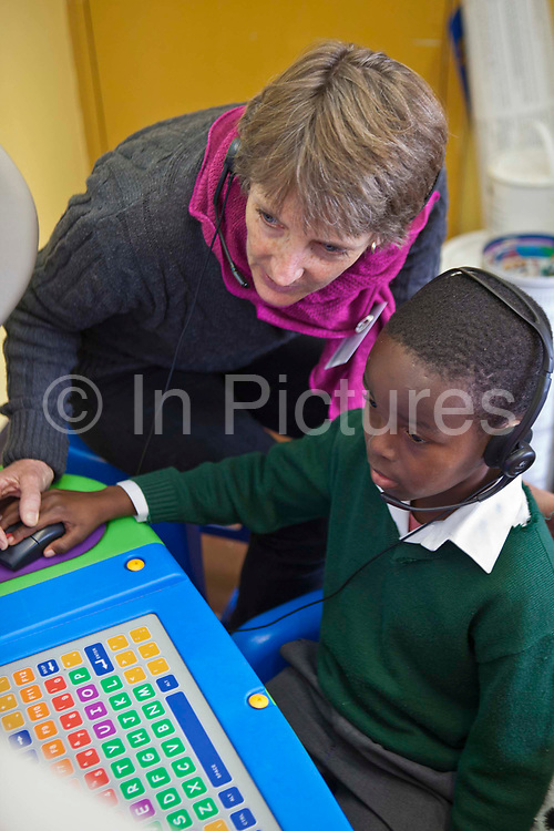 A young African school boy uses a computer with a literacy teacher in a classroom in Lourier Primary School, Cape Town, South Africa.  The teacher is helping the pupil complete a reading task.  The computer and volunteer teacher are provided by the Life Matters organisation which is partnered with the Shine Centre which is a charity that aims to address the high illiteracy rate in South Africa by improving literacy levels among children in schools and disadvantaged communities.