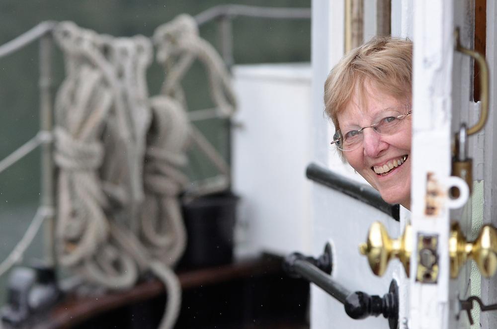 Woman peeking out door of small cruise boat in Southeast Alaska.