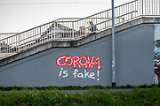 "A graffiti ""Corona is Fake"" sprayed against a wall at the S-Bahn station Oberursel-Stierstadt."