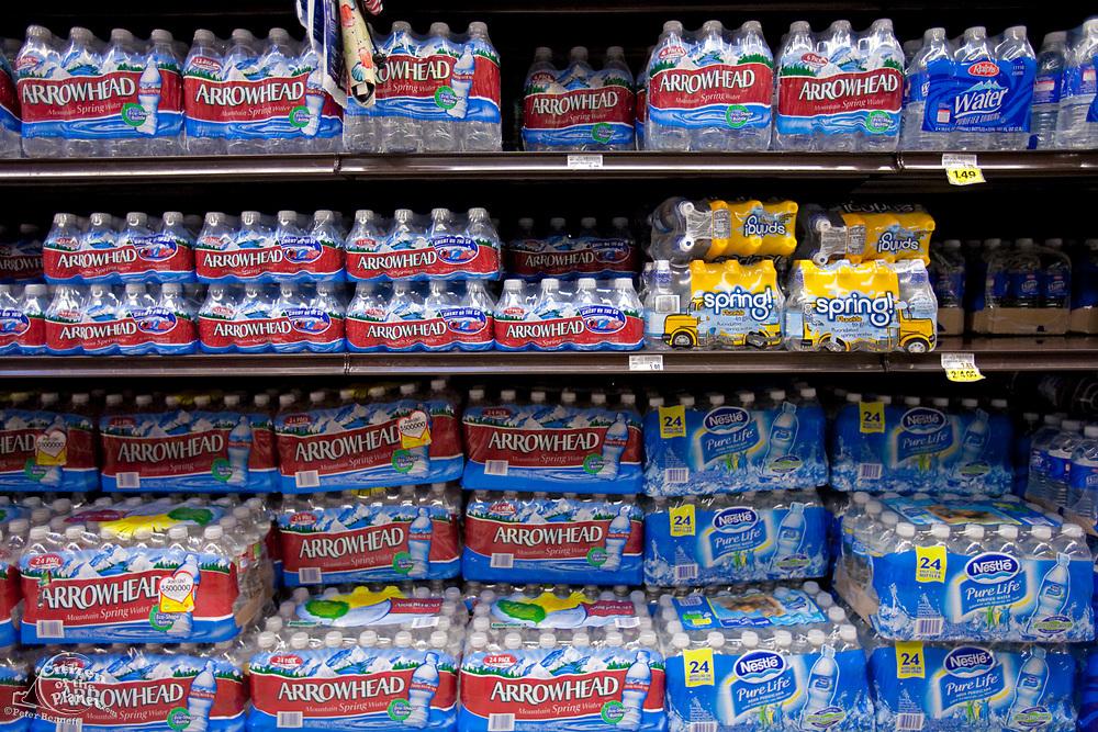 Plastic water bottles on shelves of supermarket, Los Angeles, California, USA