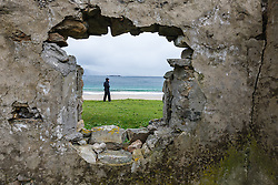 View through hole in stone wall to man watching waves, Keem Bay, Achill Island, County Mayo, Ireland