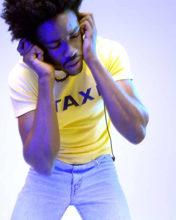 Portrait of a black male wearing yellow t-shirt and jeans dancing and listening to his music on his headphones