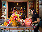 12 JANUARY 2017 - BANGKOK, THAILAND:       A woman makes an offering at a Chinese Buddhist shrine for vendors in Bo Bae Market. Bo Bae Market is a sprawling wholesale clothing market in Bangkok. There are reportedly more than 1,200 stalls selling clothes made in Thailand and neighboring countries. Bangkok officials have threatened to shut down parts of Bo Bae market, but so far it has escaped the fate of the other street markets that have been shut down.     PHOTO BY JACK KURTZ