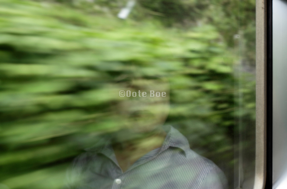 female person reflecting in the window of a traveling train