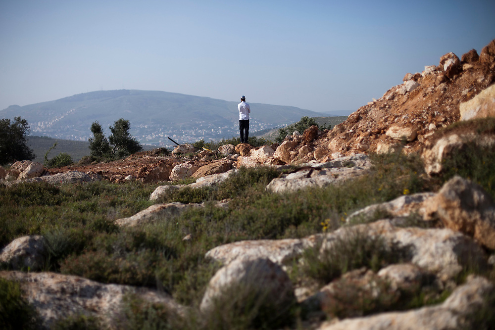 An Orthodox Jewish man watches the view in the West Bank settlement of Itamar on April 10, 2011, prior to a memorial service marking 30 days since the murder of five members of the Fogel family, including three children, who were stabbed to death in their beds as they slept in the West Bank settlement of Itamar.