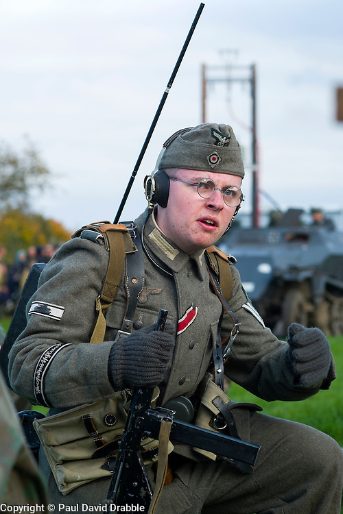 A Re-enactor portraying a Obergefreiter of the Grossdeutschland Panzer Grenadier Division  during a battle battle re-enactment on Pickering Showground. He is wearing an Iron Cross 2nd Class ribbon and Tank destruction Badge on his sleeve. He carrying a Field radio and wears a side cap and earphones<br /> <br /> 17/18 October 2015<br />  Image © Paul David Drabble <br />  www.pauldaviddrabble.co.uk