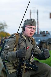 A Re-enactor portraying a Obergefreiter of the Grossdeutschland Panzer Grenadier Division  during a battle battle re-enactment on Pickering Showground. He is wearing an Iron Cross 2nd Class ribbon and Tank destruction Badge on his sleeve. He carrying a Field radio and wears a side cap and earphones<br />