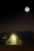 A full moon looms over a a warehouse at night in Livermore, California.