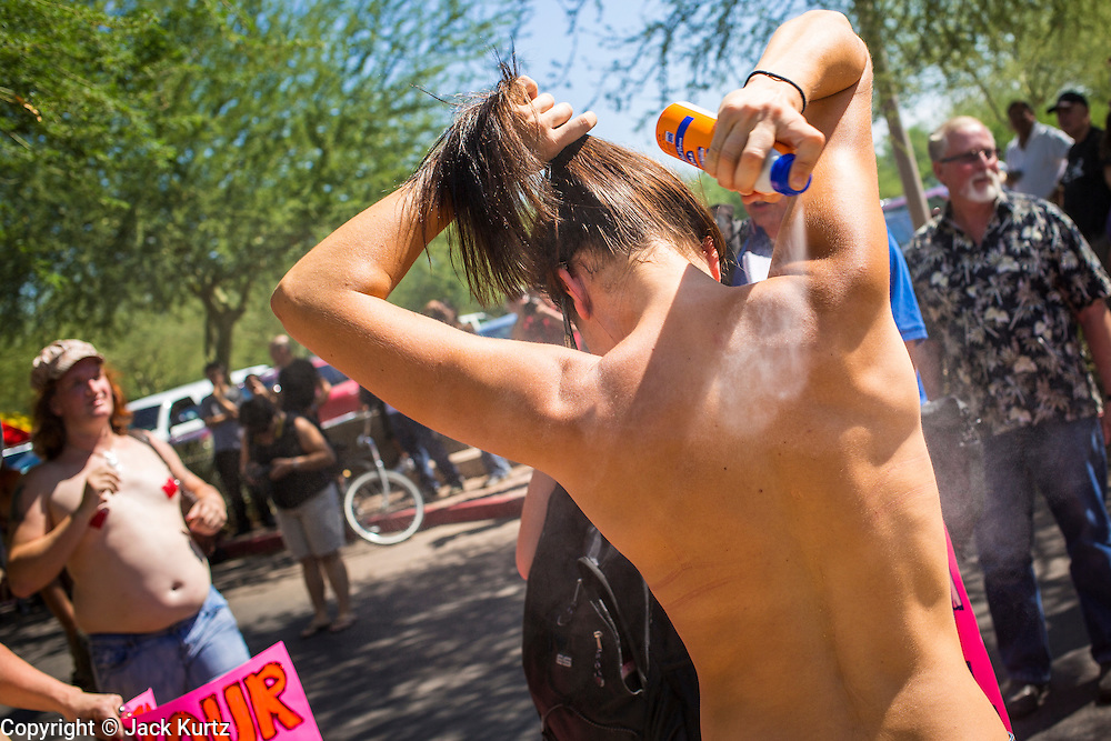 26 MARCH 2012 - PHOENIX, AZ: MEGAN ERBE, from Phoenix, sprays on sunblock before marching in a topless protest in Phoenix. About 40 people marched through central Phoenix Sunday to call for a constitutional amendment to give women the same right to go shirtless in public that men have. The Phoenix demonstration was a part of a national Topless Day of Protest. Phoenix prohibits women from going topless in public so protesters, women and men, covered their nipples and areolas with tape. The men did it to show solidarity with the women marchers.    PHOTO BY JACK KURTZ