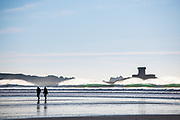 Silhouette of a couple walking past the waves breaking in front of La Rocco Tower at St Ouen's Bay, Jersey, CI on a cold winter afternoon.