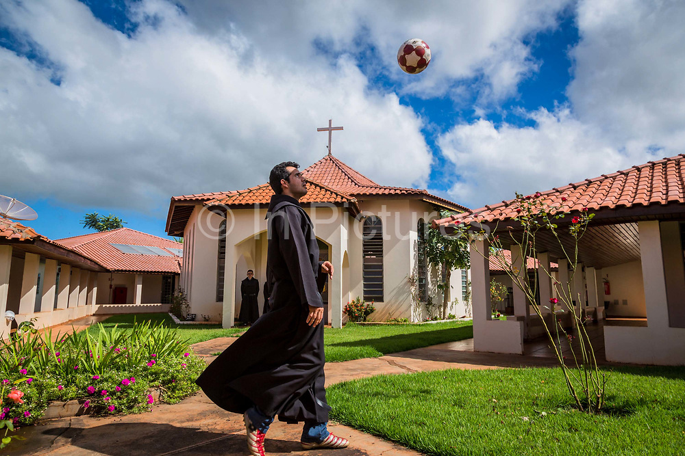 A priest of the Santo Tomás de Villanova seminary, Ourinhos, Brazil kicks about a football in its courtyard.The priests football team has won many local trophies and is considered amongst the best team in the region.