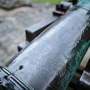 Details etched into a metal cannon at Caernarfon Castle in northwest Wales. A castle originally stood on the site dating back to the late 11th century, but in the late 13th century King Edward I commissioned a new structure that stands to this day. It has distinctive towers and is one of the best preserved of the series of castles Edward I commissioned.
