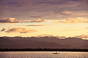 Fishermen in Gumacas bay and the Sierra Madre mountain range at dawn after having spent the whole night fishing, Aurora province, Philippines