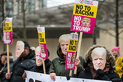 © Licensed to London News Pictures. 20/01/2018. London, UK. Protesters wearing Donald Trump masks at a demonstration outside the new American Embassy in Nine Elms on the first anniversary of Trump's inauguration as US President. Trump has cancelled his planned February 2018 visit to the UK and has described the new embassy as a 'bad deal'. Photo credit: Rob Pinney/LNP