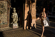 Shopping woman passes-by gallery with small girl statue credited to 19th century Florence-born artist Raffaello Romanelli.